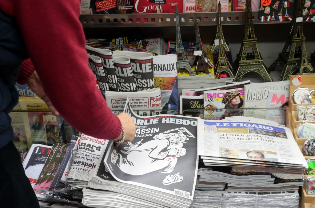 "A woman looks at the special commemorative edition of French satirical newspaper Charlie Hebdo at a newsstand in Paris, on January 6, 2015, to mark the one-year anniversary of the jihadist attack that claimed the lives of 12 people, including three of its best-known cartoonists. True to form, the cover is unabashedly provocative, featuring a Kalashnikov-toting God figure wearing a blood-stained white robe, under the headline: ""One year on: The killer is still at large."" / AFP / JACQUES DEMARTHON"