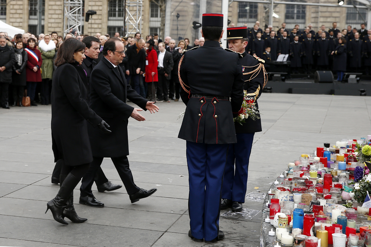 (From L) Mayor of Paris Anne Hidalgo, French President Francois Hollande and French Prime Minister Manuel Valls attend a remembrance rally at Place de la Republique (Republic square) on January 10, 2016 to mark a year since 1.6 million people thronged the French capital in a show of unity after attacks on the Charlie Hebdo newspaper and a Jewish supermarket. Just as it was last year, the vast Place de la Republique will be the focus of the gathering as people reiterate their support for freedom of expression and remember the other victims of what would become a year of jihadist outrages in France, culminating in the November 13 coordinated shootings and suicide bombings that killed 130 people and were claimed by the Islamic State (IS) group. / AFP / POOL / YOAN VALAT