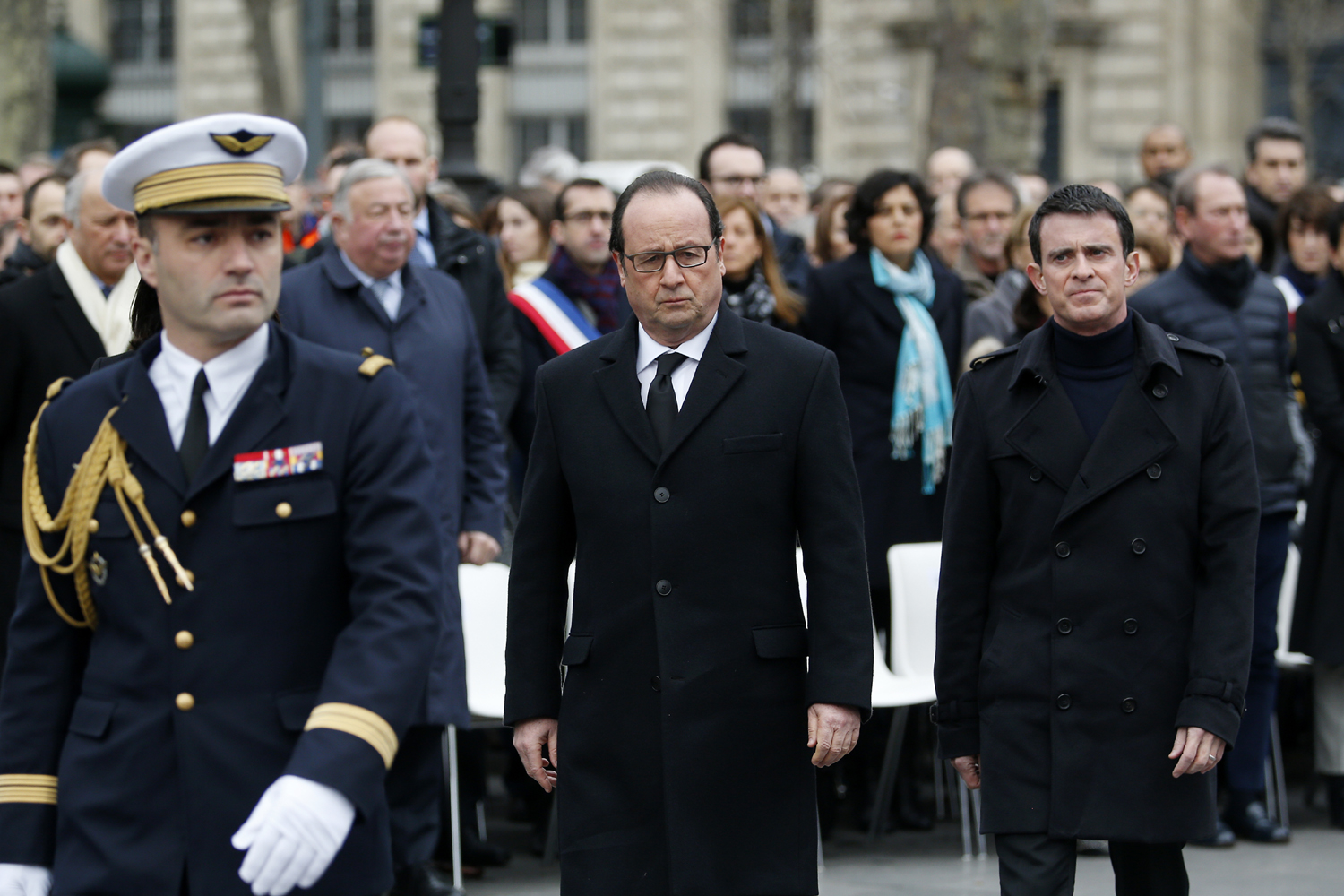 French President Francois Hollande (C) and French Prime Minister Manuel Valls (R) attend a remembrance rally at Place de la Republique (Republic square) on January 10, 2016 to mark a year since 1.6 million people thronged the French capital in a show of unity after attacks on the Charlie Hebdo newspaper and a Jewish supermarket. Just as it was last year, the vast Place de la Republique will be the focus of the gathering as people reiterate their support for freedom of expression and remember the other victims of what would become a year of jihadist outrages in France, culminating in the November 13 coordinated shootings and suicide bombings that killed 130 people and were claimed by the Islamic State (IS) group. / AFP / POOL / YOAN VALAT