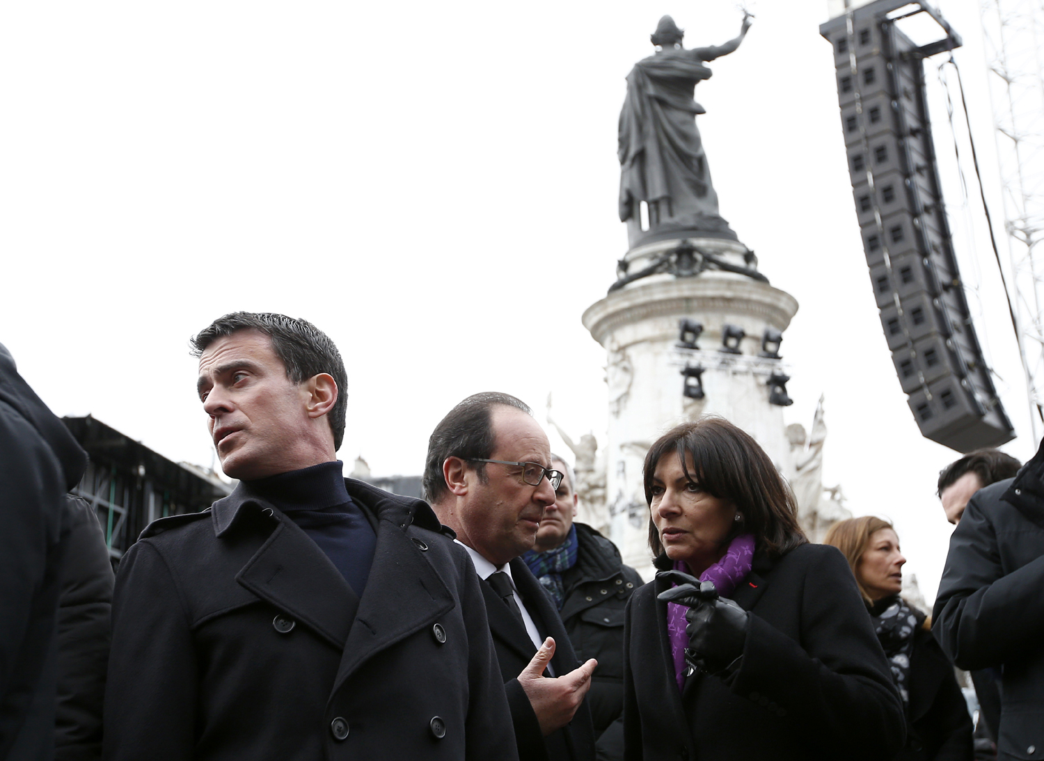 (From L) French Prime minister Manuel Valls, French President Francois Hollande and French Paris' mayor Anne Hidalgo attend a remembrance rally at Place de la Republique (Republic square) on January 10, 2016 to mark a year since 1.6 million people thronged the French capital in a show of unity after attacks on the Charlie Hebdo newspaper and a Jewish supermarket. Just as it was last year, the vast Place de la Republique will be the focus of the gathering as people reiterate their support for freedom of expression and remember the other victims of what would become a year of jihadist outrages in France, culminating in the November 13 coordinated shootings and suicide bombings that killed 130 people and were claimed by the Islamic State (IS) group. / AFP / YOAN VALAT