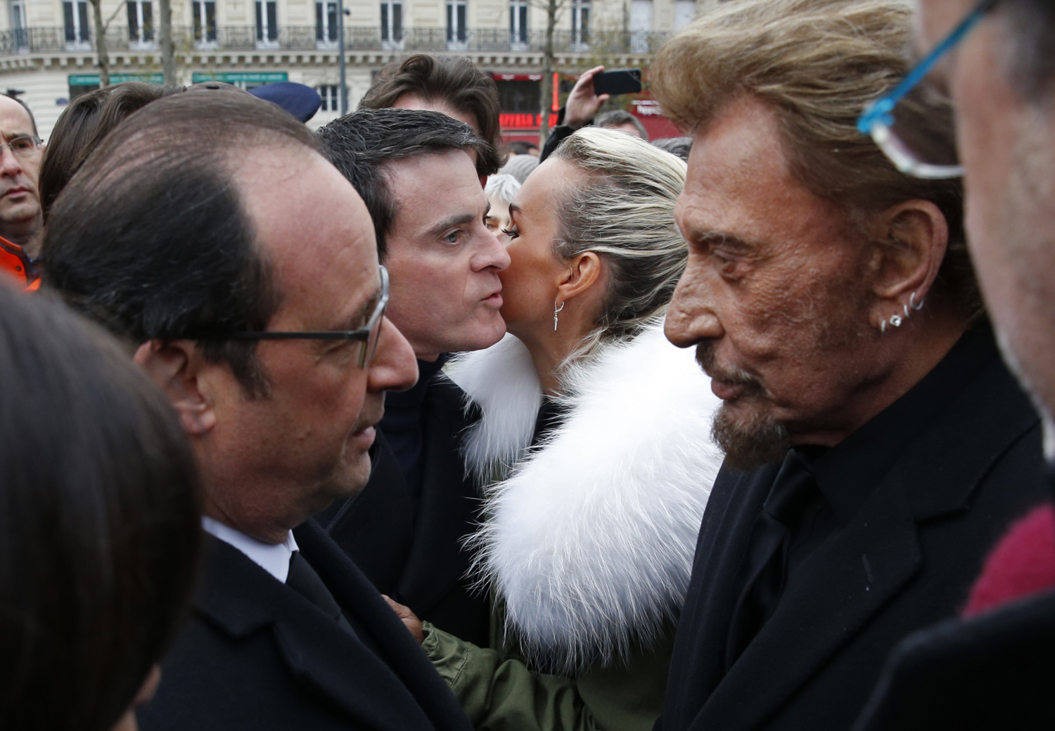 French President Francois Hollande (L) speaks with French singer Johnny Hallyday (R) as Prime Minister Manuel Valls (2ndL) kisses Hallyday's wife Laeticia at the end of a ceremony held on January 10, 2016 to mark a year since 1.6 million people thronged the French capital in a show of unity after attacks on the Charlie Hebdo newspaper and a Jewish supermarket. Just as it was last year, the vast Place de la Republique will be the focus of the gathering as people reiterate their support for freedom of expression and remember the other victims of what would become a year of jihadist outrages in France, culminating in the November 13 coordinated shootings and suicide bombings that killed 130 people and were claimed by the Islamic State (IS) group. / AFP / POOL / PHILIPPE WOJAZER