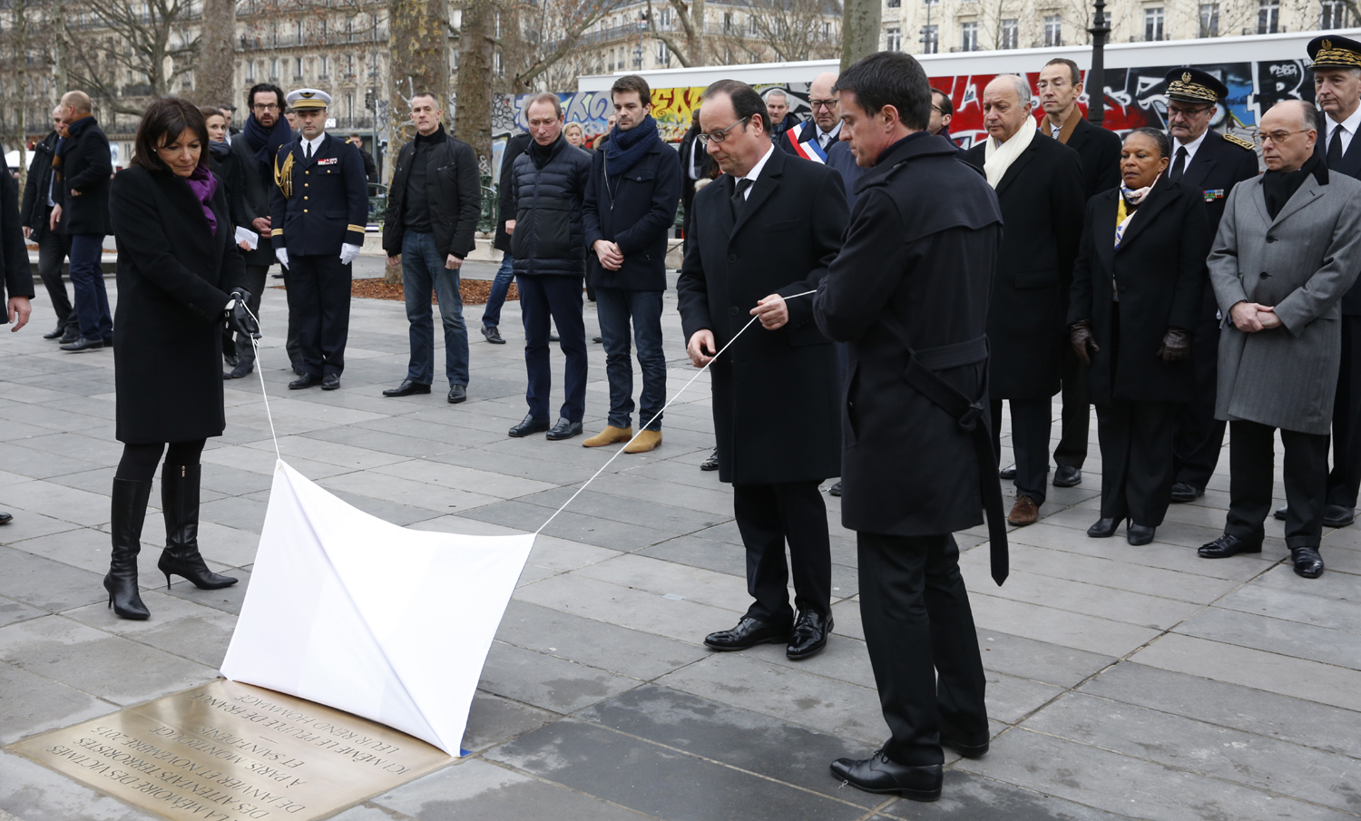 French President Francois Hollande (C), Prime Minister Manuel Valls (R) and Paris Mayor Anne Hidalgo (L) unveil a commemorative plaque during a ceremony held, on January 10, 2016 to mark a year since 1.6 million people thronged the French capital in a show of unity after attacks on the Charlie Hebdo newspaper and a Jewish supermarket. Just as it was last year, the vast Place de la Republique will be the focus of the gathering as people reiterate their support for freedom of expression and remember the other victims of what would become a year of jihadist outrages in France, culminating in the November 13 coordinated shootings and suicide bombings that killed 130 people and were claimed by the Islamic State (IS) group. / AFP / POOL / PHILIPPE WOJAZER