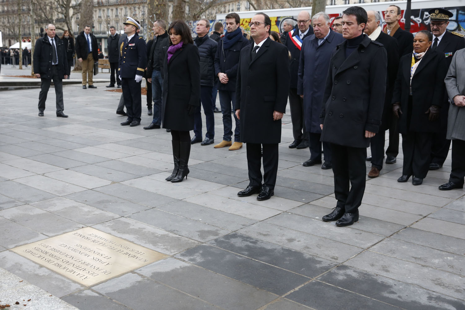 French President Francois Hollande (C), Prime Minister Manuel Valls (R) and Paris Mayor Anne Hidalgo (L) pay respect after unveiling a commemorative plaque during a ceremony held, on January 10, 2016 to mark a year since 1.6 million people thronged the French capital in a show of unity after attacks on the Charlie Hebdo newspaper and a Jewish supermarket. Just as it was last year, the vast Place de la Republique will be the focus of the gathering as people reiterate their support for freedom of expression and remember the other victims of what would become a year of jihadist outrages in France, culminating in the November 13 coordinated shootings and suicide bombings that killed 130 people and were claimed by the Islamic State (IS) group. / AFP / POOL / PHILIPPE WOJAZER
