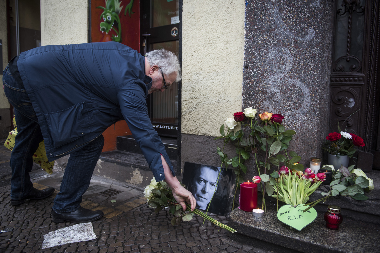 David-Bowie-fan Dirk Turnage puts down a tribute to British rock legend David Bowie outside his former home in Berlin's Hauptstrasse 155 on January 11, 2016. British rock music legend David Bowie has died after a long battle with cancer, his official Twitter and Facebook accounts said. / AFP / ODD ANDERSEN