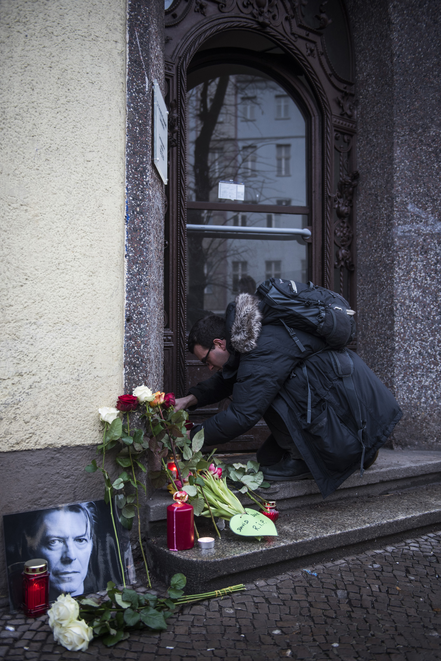 David-Bowie-fan Jamie Young puts down a tribute to British rock legend David Bowie outside his former home in Berlin's Hauptstrasse 155 on January 11, 2016. British rock music legend David Bowie has died after a long battle with cancer, his official Twitter and Facebook accounts said. / AFP / ODD ANDERSEN