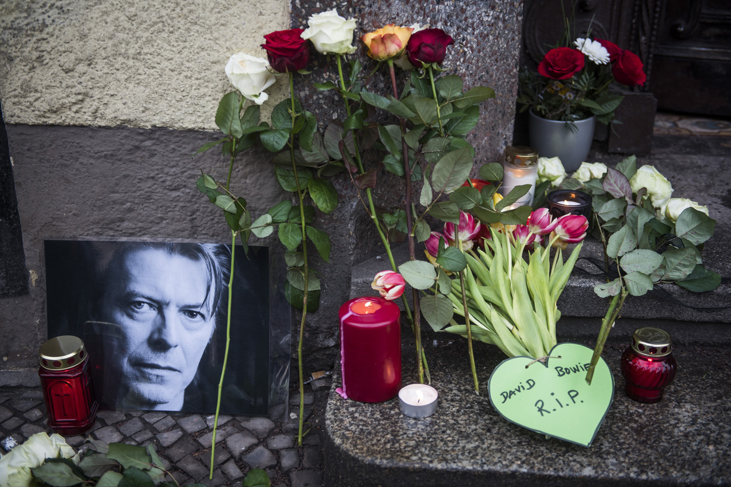 Tributes to British rock legend David Bowie are seen outside his former home in Berlin's Hauptstrasse 155 on January 11, 2016. British rock music legend David Bowie has died after a long battle with cancer, his official Twitter and Facebook accounts said. / AFP / ODD ANDERSEN