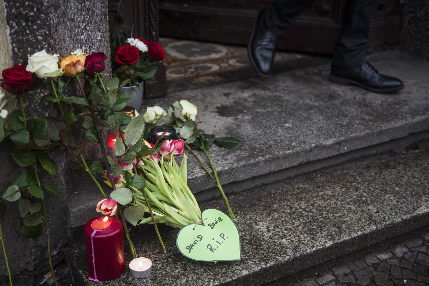 A resident leaves the building among tributes to British rock legend David Bowie leftoutside his former home in Berlin's Hauptstrasse 155 on January 11, 2016. British rock music legend David Bowie has died after a long battle with cancer, his official Twitter and Facebook accounts said. / AFP / ODD ANDERSEN