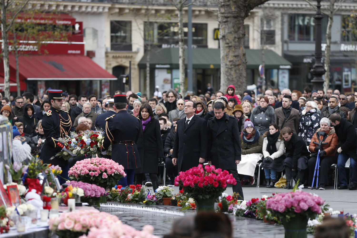 French Paris' mayor Anne Hidalgo (C-L), French President Francois Hollande (C) and French Prime minister Manuel Valls (C-R), attend a remembrance rally at Place de la Republique (Republic square) on January 10, 2016 in Paris, to mark a year since 1.6 million people thronged the French capital in a show of unity after attacks on the Charlie Hebdo newspaper and a Jewish supermarket. Just as it was last year, the vast Place de la Republique will be the focus of the gathering as people reiterate their support for freedom of expression and remember the other victims of what would become a year of jihadist outrages in France, culminating in the November 13 coordinated shootings and suicide bombings that killed 130 people and were claimed by the Islamic State (IS) group. AFP PHOTO / THOMAS SAMSON / AFP / THOMAS SAMSON