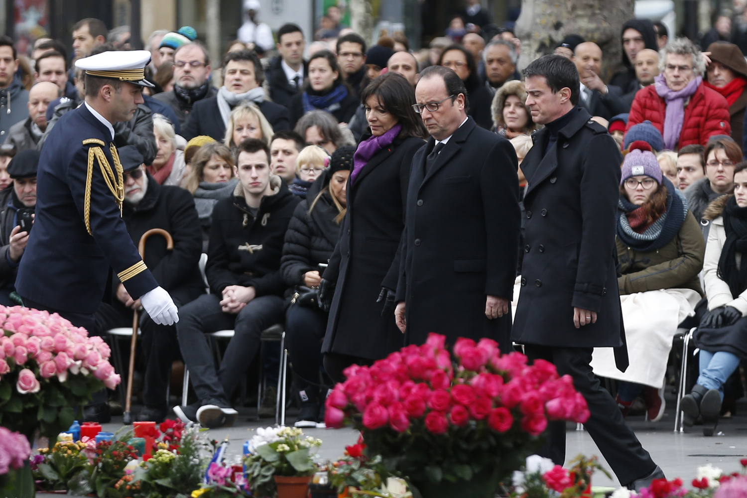 French Paris' mayor Anne Hidalgo (C), French President Francois Hollande (2ndR) and French Prime minister Manuel Valls (R) walk during a remembrance rally at Place de la Republique (Republic square) on January 10, 2016 in Paris, to mark a year since 1.6 million people thronged the French capital in a show of unity after attacks on the Charlie Hebdo newspaper and a Jewish supermarket. Just as it was last year, the vast Place de la Republique will be the focus of the gathering as people reiterate their support for freedom of expression and remember the other victims of what would become a year of jihadist outrages in France, culminating in the November 13 coordinated shootings and suicide bombings that killed 130 people and were claimed by the Islamic State (IS) group. AFP PHOTO / THOMAS SAMSON / AFP / THOMAS SAMSON