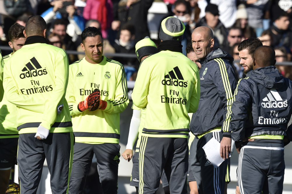 """Real Madrid's new French coach Zinedine Zidane (3rdR) speaks with his players during his first training session as coach of Real Madrid at the Alfredo di Stefano stadium in Valdebebas, on the outskirts of Madrid, on January 5, 2016. Real Madrid legend Zinedine Zidane promised to put his """"heart and soul"""" into managing the Spanish giants after he was sensationally named as coach following Rafael Benitez's unceremonious sacking. AFP PHOTO/ GERARD JULIEN / AFP / GERARD JULIEN"""