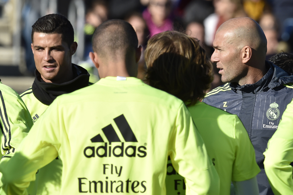 """Real Madrid's new French coach Zinedine Zidane (R) looks at Real Madrid's Portuguese forward Cristiano Ronaldo during his first training session as coach of Real Madrid at the Alfredo di Stefano stadium in Valdebebas, on the outskirts of Madrid, on January 5, 2016. Real Madrid legend Zinedine Zidane promised to put his """"heart and soul"""" into managing the Spanish giants after he was sensationally named as coach following Rafael Benitez's unceremonious sacking. AFP PHOTO/ GERARD JULIEN / AFP / GERARD JULIEN"""