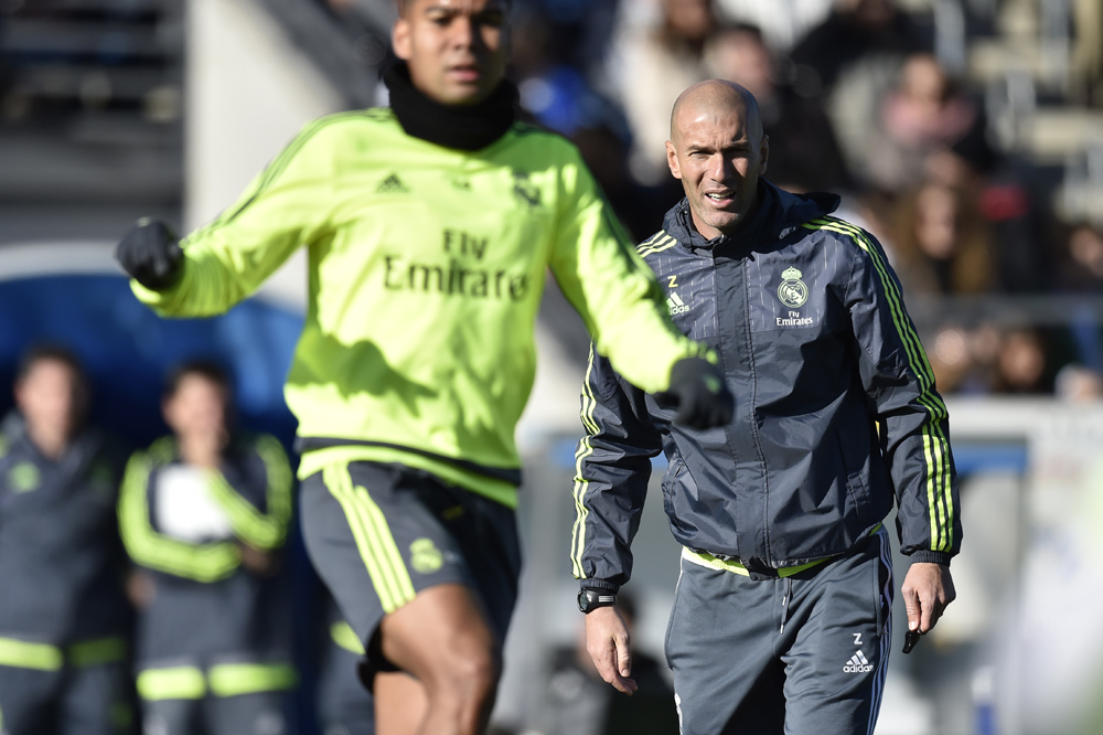 """Real Madrid's new French coach Zinedine Zidane (R) looks at his players during his first training session as coach of Real Madrid at the Alfredo di Stefano stadium in Valdebebas, on the outskirts of Madrid, on January 5, 2016. Real Madrid legend Zinedine Zidane promised to put his """"heart and soul"""" into managing the Spanish giants after he was sensationally named as coach following Rafael Benitez's unceremonious sacking. AFP PHOTO/ GERARD JULIEN / AFP / GERARD JULIEN"""