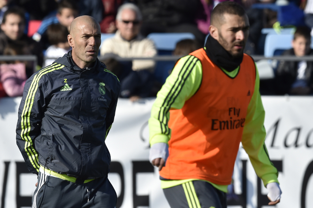 """Real Madrid's new French coach Zinedine Zidane (L) looks at his players during his first training session as coach of Real Madrid at the Alfredo di Stefano stadium in Valdebebas, on the outskirts of Madrid, on January 5, 2016. Real Madrid legend Zinedine Zidane promised to put his """"heart and soul"""" into managing the Spanish giants after he was sensationally named as coach following Rafael Benitez's unceremonious sacking. AFP PHOTO/ GERARD JULIEN / AFP / GERARD JULIEN"""