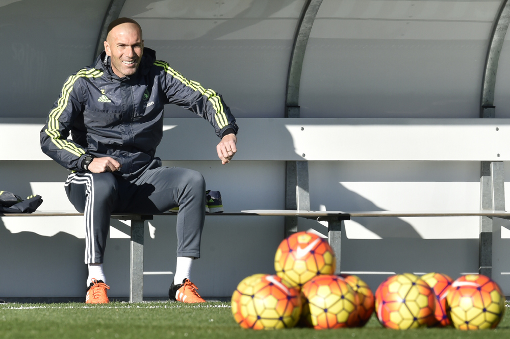 """Real Madrid's new French coach Zinedine Zidane gestures as he sits on a bench during his first training session as coach of Real Madrid at the Alfredo di Stefano stadium in Valdebebas, on the outskirts of Madrid, on January 5, 2016. Real Madrid legend Zinedine Zidane promised to put his """"heart and soul"""" into managing the Spanish giants after he was sensationally named as coach following Rafael Benitez's unceremonious sacking. AFP PHOTO/ GERARD JULIEN / AFP / GERARD JULIEN"""