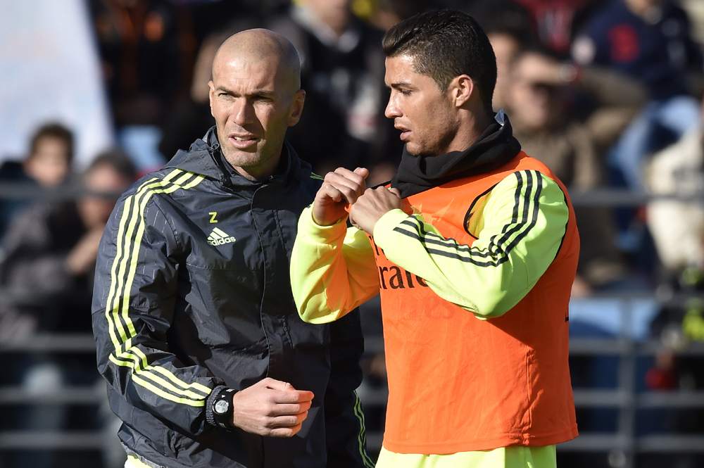"Real Madrid's new French coach Zinedine Zidane (L) and Real Madrid's Portuguese forward Cristiano Ronaldo gesture during his first training session as coach of Real Madrid at the Alfredo di Stefano stadium in Valdebebas, on the outskirts of Madrid, on January 5, 2016. Real Madrid legend Zinedine Zidane promised to put his ""heart and soul"" into managing the Spanish giants after he was sensationally named as coach following Rafael Benitez's unceremonious sacking. AFP PHOTO/ GERARD JULIEN / AFP / GERARD JULIEN"