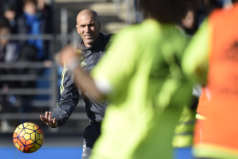 """Real Madrid's new French coach Zinedine Zidane throws a ball during his first training session as coach of Real Madrid at the Alfredo di Stefano stadium in Valdebebas, on the outskirts of Madrid, on January 5, 2016. Real Madrid legend Zinedine Zidane promised to put his """"heart and soul"""" into managing the Spanish giants after he was sensationally named as coach following Rafael Benitez's unceremonious sacking. AFP PHOTO/ GERARD JULIEN / AFP / GERARD JULIEN"""