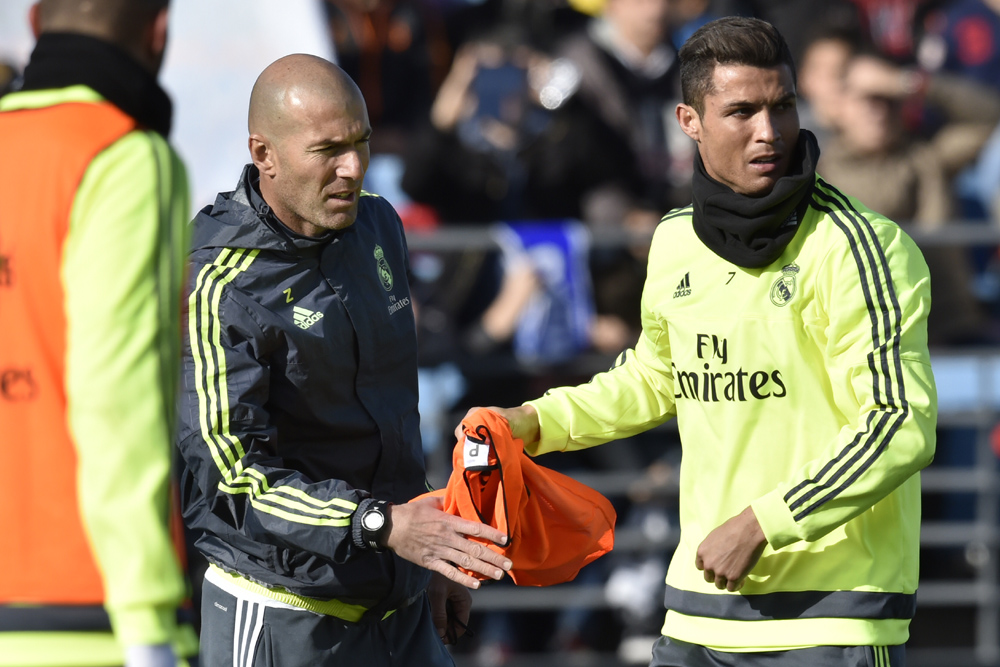"""Real Madrid's Portuguese forward Cristiano Ronaldo (R) gives a bib to Real Madrid's new French coach Zinedine Zidane during his first training session as coach of Real Madrid at the Alfredo di Stefano stadium in Valdebebas, on the outskirts of Madrid, on January 5, 2016. Real Madrid legend Zinedine Zidane promised to put his """"heart and soul"""" into managing the Spanish giants after he was sensationally named as coach following Rafael Benitez's unceremonious sacking. AFP PHOTO/ GERARD JULIEN / AFP / GERARD JULIEN"""