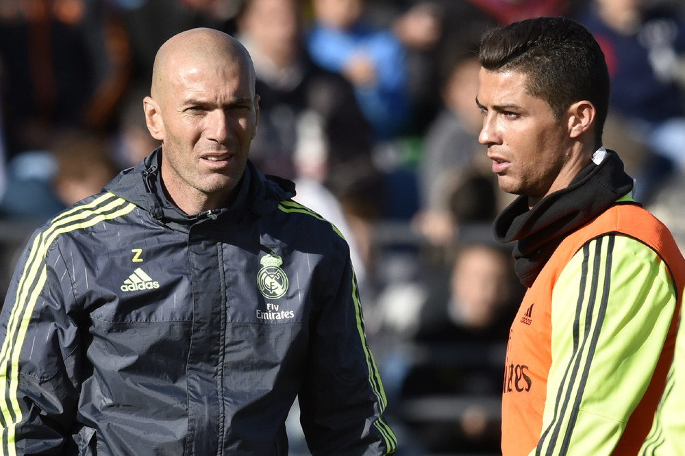 """Real Madrid's new French coach Zinedine Zidane (L) walks past Real Madrid's Portuguese forward Cristiano Ronaldo during his first training session as coach of Real Madrid at the Alfredo di Stefano stadium in Valdebebas, on the outskirts of Madrid, on January 5, 2016. Real Madrid legend Zinedine Zidane promised to put his """"heart and soul"""" into managing the Spanish giants after he was sensationally named as coach following Rafael Benitez's unceremonious sacking. AFP PHOTO/ GERARD JULIEN / AFP / GERARD JULIEN"""