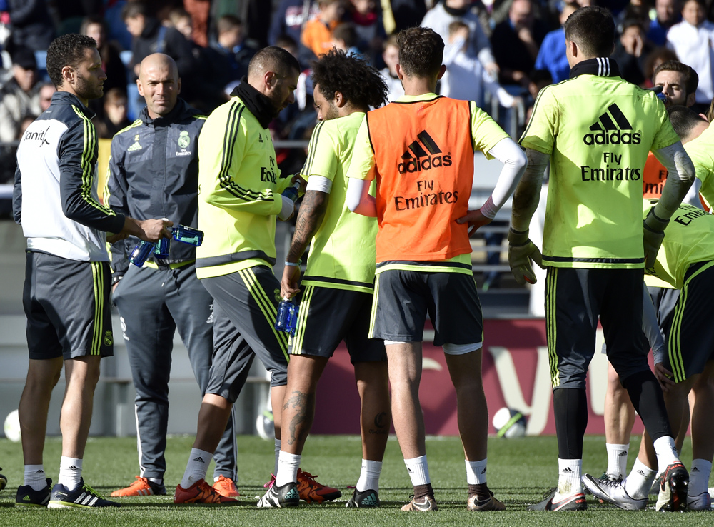 """Real Madrid's new French coach Zinedine Zidane (2ndL) stands past his players during his first training session as coach of Real Madrid at the Alfredo di Stefano stadium in Valdebebas, on the outskirts of Madrid, on January 5, 2016. Real Madrid legend Zinedine Zidane promised to put his """"heart and soul"""" into managing the Spanish giants after he was sensationally named as coach following Rafael Benitez's unceremonious sacking. AFP PHOTO/ GERARD JULIEN / AFP / GERARD JULIEN"""