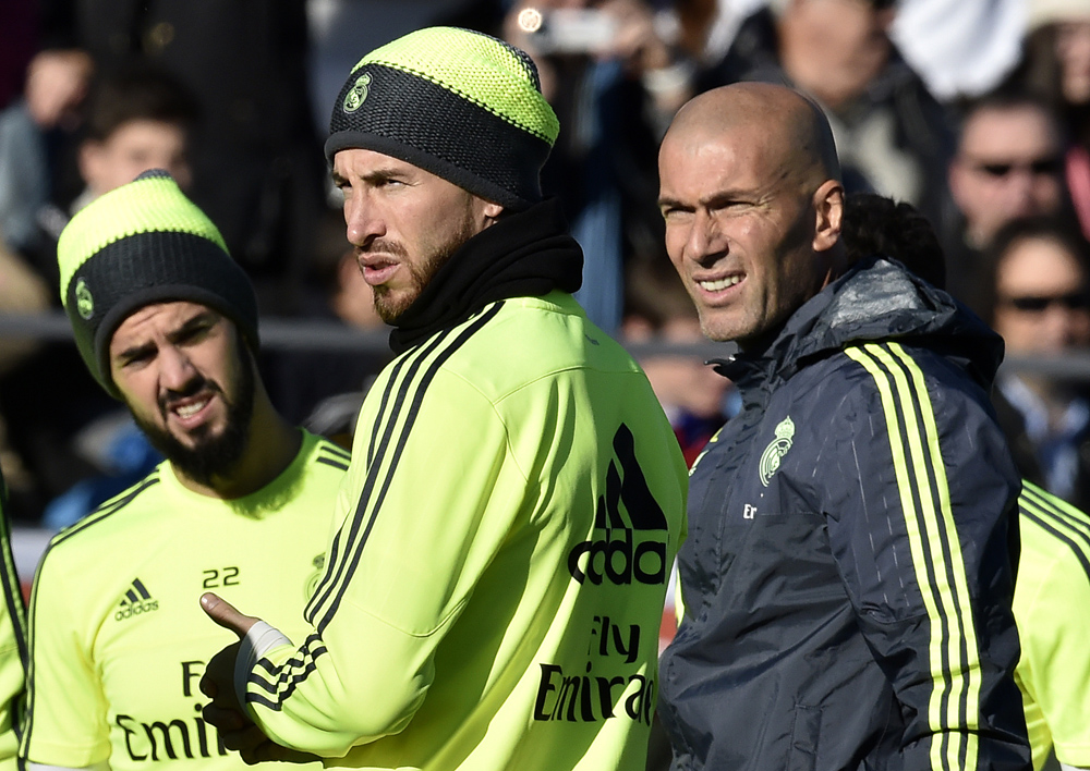 """Real Madrid's new French coach Zinedine Zidane (R) looks on past Real Madrid's defender Sergio Ramos (C) during his first training session as coach of Real Madrid at the Alfredo di Stefano stadium in Valdebebas, on the outskirts of Madrid, on January 5, 2016. Real Madrid legend Zinedine Zidane promised to put his """"heart and soul"""" into managing the Spanish giants after he was sensationally named as coach following Rafael Benitez's unceremonious sacking. AFP PHOTO/ GERARD JULIEN / AFP / GERARD JULIEN"""
