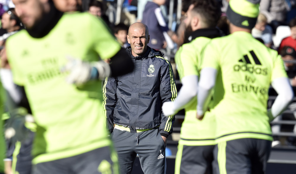 """Real Madrid's new French coach Zinedine Zidane (C) looks at his players during his first training session as coach of Real Madrid at the Alfredo di Stefano stadium in Valdebebas, on the outskirts of Madrid, on January 5, 2016. Real Madrid legend Zinedine Zidane promised to put his """"heart and soul"""" into managing the Spanish giants after he was sensationally named as coach following Rafael Benitez's unceremonious sacking. AFP PHOTO/ GERARD JULIEN / AFP / GERARD JULIEN"""