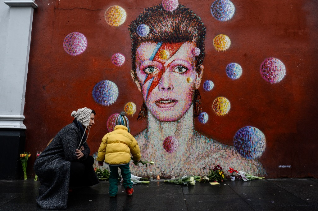 """Floral tributes are left beneath a mural of British singer David Bowie, painted by Australian street artist James Cochran, aka Jimmy C, following the announcement of Bowie's death, in Brixton, south London, on January 11, 2016. British music icon David Bowie died of cancer at the age of 69, drawing an outpouring of tributes for the innovative star famed for groundbreaking hits like """"Ziggy Stardust"""" and his theatrical shape-shifting style. AFP PHOTO / CHRIS RATCLIFFE RESTRICTED TO EDITORIAL USE, MANDATORY MENTION OF THE ARTIST UPON PUBLICATION, TO ILLUSTRATE THE EVENT AS SPECIFIED IN THE CAPTION / AFP / CHRIS RATCLIFFE"""