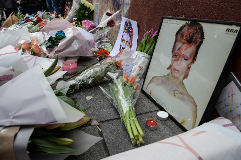 "Tributes are seen beneath a mural of British singer David Bowie, following the announcement of Bowie's death, in Brixton, south London, on January 11, 2016. British music icon David Bowie died of cancer at the age of 69, drawing an outpouring of tributes for the innovative star famed for groundbreaking hits like ""Ziggy Stardust"" and his theatrical shape-shifting style. AFP PHOTO / CHRIS RATCLIFFE / AFP / CHRIS RATCLIFFE"