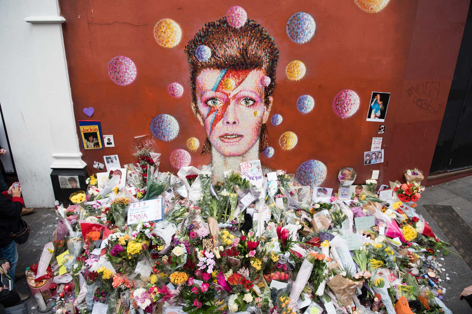 "Floral tributes are seen beneath a mural of British singer David Bowie, painted by Australian street artist James Cochran, aka Jimmy C, the day after the announcement of Bowie's death, in Brixton, south London, on January 12, 2016. Music legend David Bowie was famously private during his lifetime -- and in death, as a string of questions about the circumstances of his passing remained unanswered. His official social media accounts had announced the shock news of his death at 69 on January 11, 2016: ""David Bowie died peacefully today surrounded by his family after a courageous 18-month battle with cancer,"" adding a request for privacy for the grieving family. / AFP / LEON NEAL"
