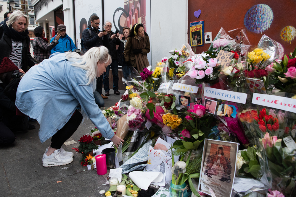 "Crowds gather to read and place floral tributes beneath a mural of British singer David Bowie, in Brixton, south London, on January 12, 2016, a day after the announcement of Bowie's death. Music legend David Bowie was famously private during his lifetime -- and in death, as a string of questions about the circumstances of his passing remained unanswered. His official social media accounts had announced the shock news of his death at 69 on January 11, 2016: ""David Bowie died peacefully today surrounded by his family after a courageous 18-month battle with cancer,"" adding a request for privacy for the grieving family. AFP PHOTO / LEON NEAL / AFP / LEON NEAL"