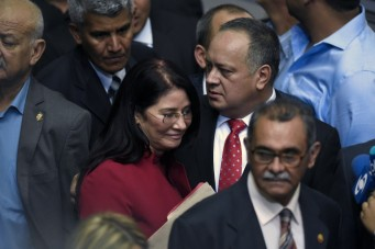 Diosdado Cabello (C), outgoing president of the National Assembly, arrives accompanied by First Lady and deputy Cilia Flores at the parliament in Caracas, on January 5, 2016. Venezuela's President Nicolas Maduro ordered the security forces to ensure the swearing-in of a new opposition-dominated legislature passes off peacefully Tuesday, after calls for rallies raised fears of unrest. AFP PHOTO/JUAN BARRETO / AFP / JUAN BARRETO