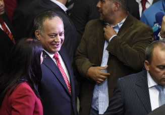 Diosdado Cabello (C), outgoing president of the National Assembly, accompanied by Venezuela's first lady, Cilia Flores (L), arrives at the parliament in Caracas, on January 5, 2016. Venezuela's President Nicolas Maduro ordered the security forces to ensure the swearing-in of a new opposition-dominated legislature passes off peacefully Tuesday, after calls for rallies raised fears of unrest. AFP PHOTO/JUAN BARRETO / AFP / JUAN BARRETO