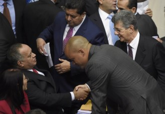 Diosdado Cabello (L), outgoing president of the National Assembly, shakes hands with the new parliament president Henry Ramos Allup (R) at the parliament in Caracas, on January 5, 2016. Venezuela's President Nicolas Maduro ordered the security forces to ensure the swearing-in of a new opposition-dominated legislature passes off peacefully Tuesday, after calls for rallies raised fears of unrest. AFP PHOTO/JUAN BARRETO / AFP / JUAN BARRETO
