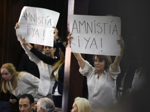 """Opposition supporters show placards that read """"Amnesty Now!"""" during the installation of the new parliament in Caracas, on January 5, 2016. Venezuela's President Nicolas Maduro ordered the security forces to ensure the swearing-in of a new opposition-dominated legislature passes off peacefully Tuesday, after calls for rallies raised fears of unrest. AFP PHOTO/JUAN BARRETO / AFP / JUAN BARRETO"""