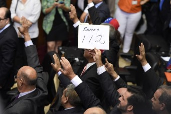 """An opposition deputy raises a placard that reads """"We are 112"""" during the new parliamentaries' swearing-in ceremony in Caracas, on January 5, 2016. Venezuela's President Nicolas Maduro ordered the security forces to ensure the swearing-in of a new opposition-dominated legislature passes off peacefully Tuesday, after calls for rallies raised fears of unrest. AFP PHOTO/JUAN BARRETO / AFP / JUAN BARRETO"""