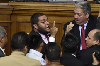 Newly elected opposition deputy Juan Requesens (C) argues with governement deputies during the new parliament's swearing-in ceremony in Caracas, on January 5, 2016. Venezuela's President Nicolas Maduro ordered the security forces to ensure the swearing-in of a new opposition-dominated legislature passes off peacefully Tuesday, after calls for rallies raised fears of unrest. AFP PHOTO/JUAN BARRETO / AFP / JUAN BARRETO