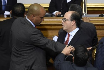 Newly elected opposition deputy Julio Borges (C) and governement deputy Hector Rodriguez (L) argue during the new parliament's swearing-in ceremony in Caracas, on January 5, 2016. Venezuela's President Nicolas Maduro ordered the security forces to ensure the swearing-in of a new opposition-dominated legislature passes off peacefully Tuesday, after calls for rallies raised fears of unrest. AFP PHOTO/JUAN BARRETO / AFP / JUAN BARRETO