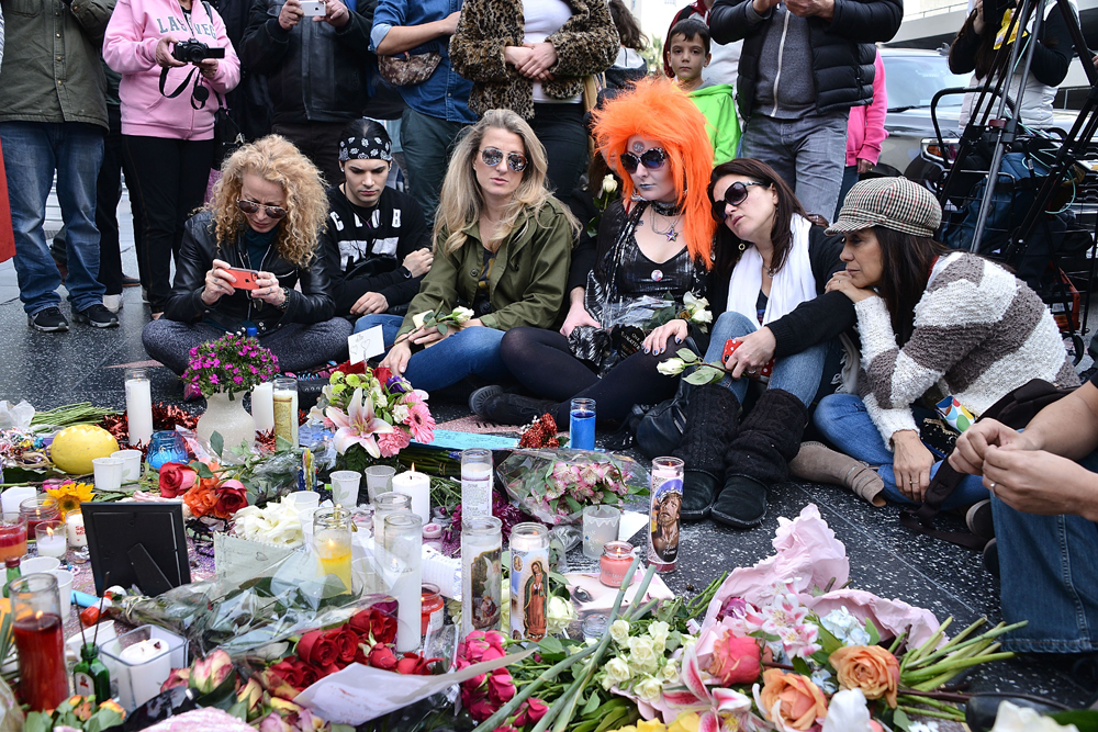 HOLLYWOOD, CA - JANUARY 11: People pay tribute at a memorial on David Bowie's star on The Hollywood Walk of Fame on January 11, 2016 in Hollywood, California. British music and fashion icon David Bowie died earlier January 10 at the age of 69 after a battle with cancer. Araya Diaz/Getty Images/AFP