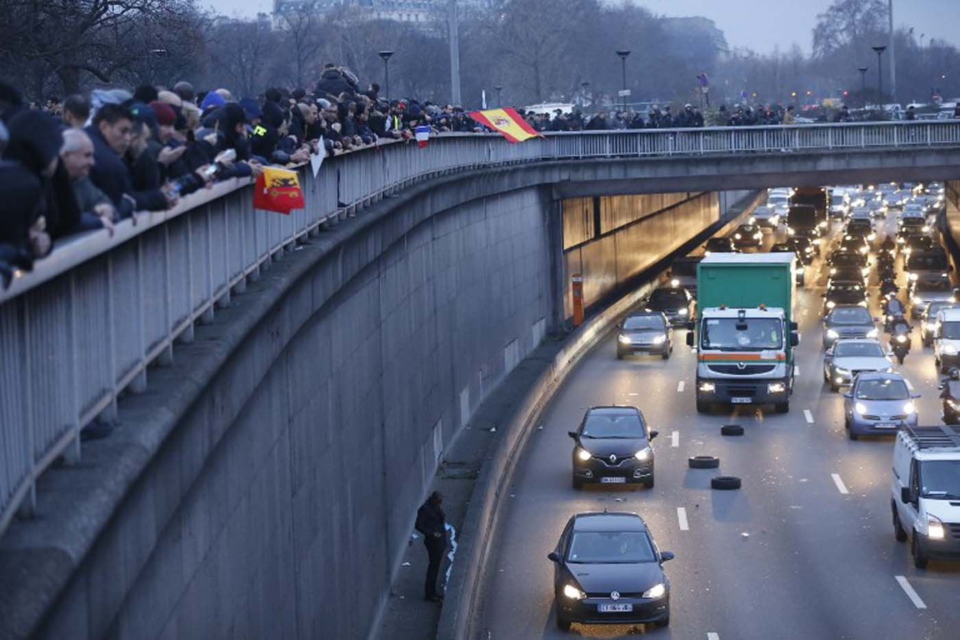 People and protestors with European countries flags stand above the ringroad (peripherique) during a taxi drivers demonstration against the VTC (transport vehicle with chauffeur) on January 26, 2016 early in the morning at porte Maillot in Paris. AFP PHOTO / THOMAS SAMSON / AFP / THOMAS SAMSON
