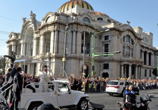 Pope Francis waves from the popemobile on his way to the Guadalupe Basilica in Mexico City on February 13, 2016. Francis will be the first pope to enter Mexico's National Palace to meet President Enrique Pena Nieto, as he starts a cross-country tour that will highlight the country's violence and migration troubles. AFP PHOTO/MARIO VAZQUEZ / AFP / MARIO VAZQUEZ