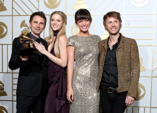 LOS ANGELES, CA - FEBRUARY 15: Recording artists Matt Bellamy (L) and Dominic Howard of music group Muse, winners of Best Rock Album for 'Drones,' models Rayana Ragan and Elle Evans pose in the press room during The 58th GRAMMY Awards at Staples Center on February 15, 2016 in Los Angeles, California. Frederick M. Brown/Getty Images for NARAS/AFP