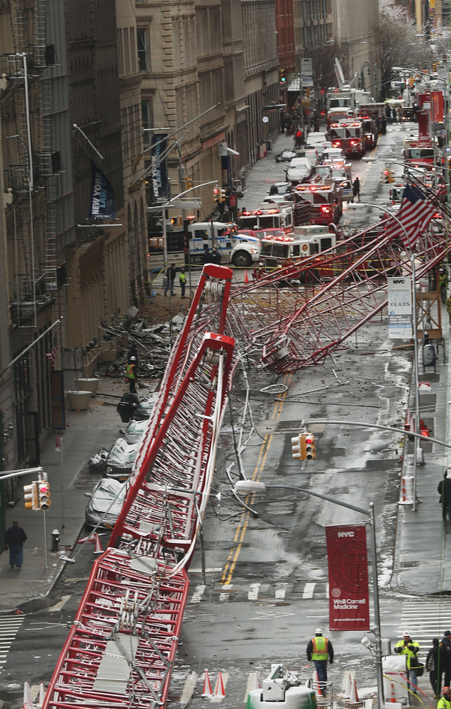 NEW YORK, NY - FEBRUARY 05: Emergency workers converge at the scene of a collapsed crane in a roadway in lower Manhattan Friday morning on February 5, 2016 in New York City. The accident killed at least one person and seriously injured two according to the New York City Fire Department.   Spencer Platt/Getty Images/AFP