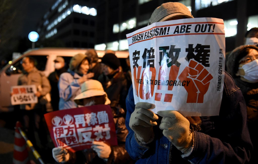 """A protester (R) holds a placard saying """"No, Abe administration"""" during an anti-nuclear demonstration rally in front of the Diet building in Tokyo on March 11, 2016. Hundreds of demonstratior staged the anti-nuclear rally on the fifth anniversary day of 2011 quake and tsunami disaster in northern Japan. / AFP / TOSHIFUMI KITAMURA"""