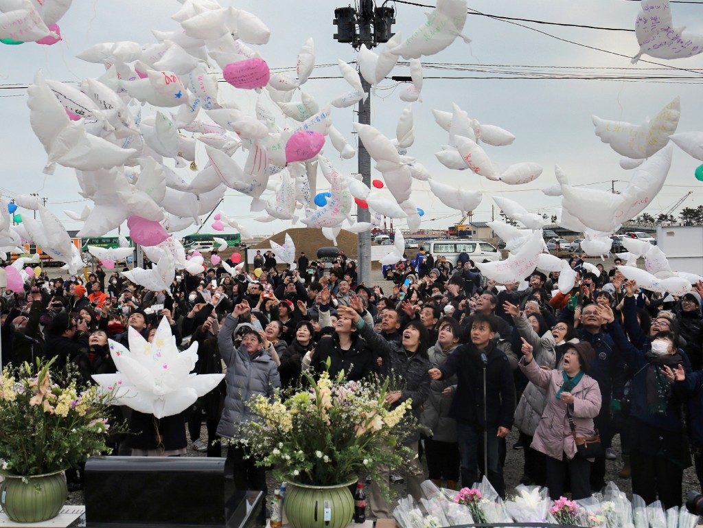 Residents release dove-shape balloons with massages for quake and tsunami victims in Natori, Miyagi prefecture on March 11, 2016. Japan pauses on March 11 to mark five years since an offshore earthquake spawned a monster tsunami that left about 18,500 people dead or missing along its northeastern coast and sparked the worst nuclear disaster in a quarter century. / AFP / JIJI PRESS / JIJI PRESS / Japan OUT