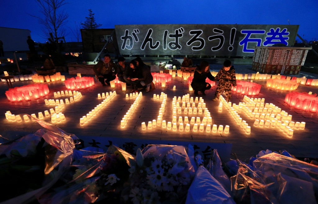 """Residents lit candles saying """"3.11 memorial"""" in Ishinomaki, Miyagi prefecture on March 11, 2016. Japan pauses on March 11 to mark five years since an offshore earthquake spawned a monster tsunami that left about 18,500 people dead or missing along its northeastern coast and sparked the worst nuclear disaster in a quarter century. / AFP / JIJI PRESS / JIJI PRESS / Japan OUT"""