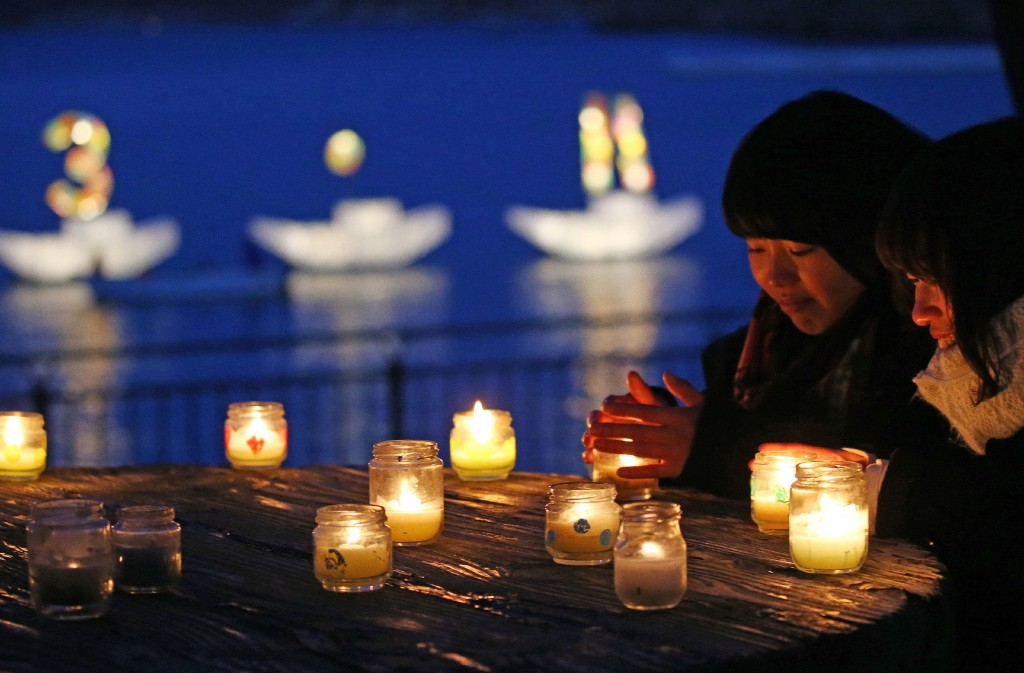 """Residents pray for the quake and tsunami victims before candle lights while a candle boat displays """"3.11"""" letters in Kamaishi, Iwate prefecture on March 11, 2016. Japan pauses on March 11 to mark five years since an offshore earthquake spawned a monster tsunami that left about 18,500 people dead or missing along its northeastern coast and sparked the worst nuclear disaster in a quarter century. / AFP / JIJI PRESS / JIJI PRESS / Japan OUT"""