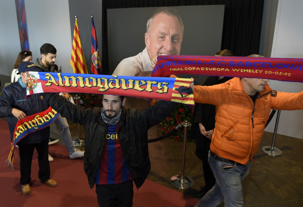 FC Barcelona football fan display scarves as they pay tribute to late Dutch football star Johan Cruyff in a special condolence area set up at Camp Nou stadium, in Barcelona on March 26, 2016. Cruyff, one of the greatest footballers of all time who dazzled with his artistry, died on March 24, 2016 at the age of 68 after losing a battle with lung cancer, prompting an avalanche of tributes from around the sports world. / AFP / LLUIS GENE