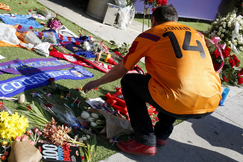 A football fan wearing a jersey of Dutch national team leaves lollipops amongst other objects as he pays tribute to late Dutch football star Johan Cruyff in a special condolence area set up at Camp Nou stadium, in Barcelona on March 26, 2016. Cruyff, one of the greatest footballers of all time who dazzled with his artistry, died on March 24, 2016 at the age of 68 after losing a battle with lung cancer, prompting an avalanche of tributes from around the sports world. / AFP / PAU BARRENA