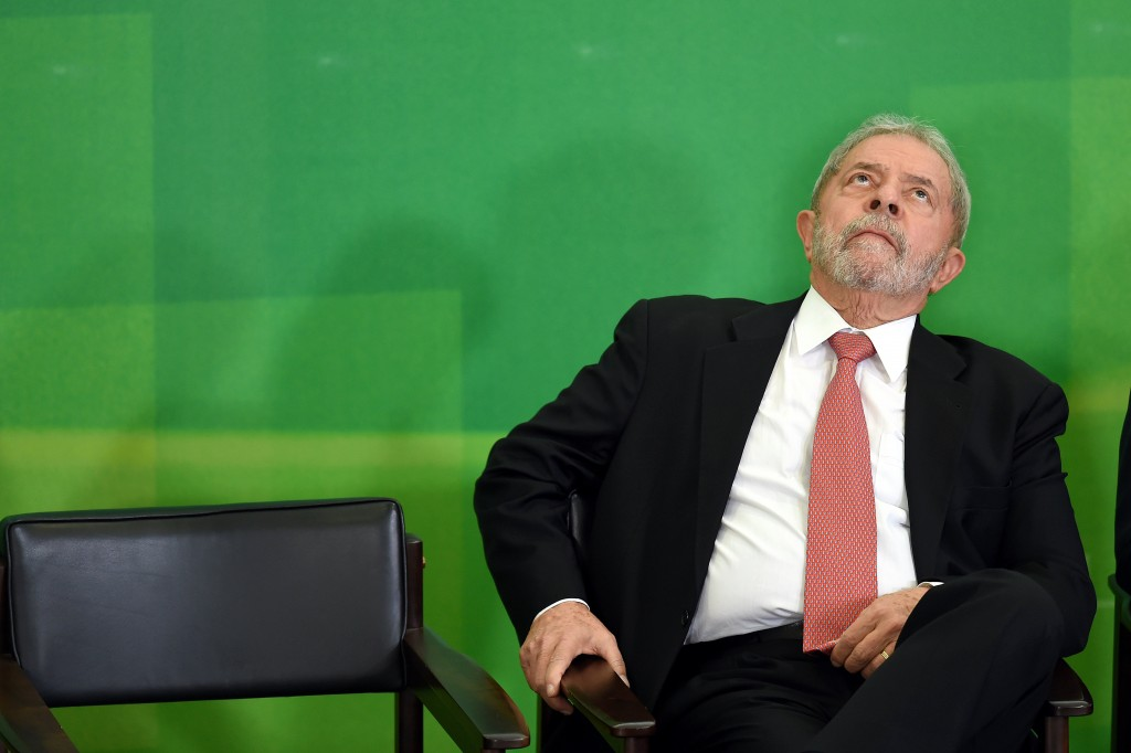 Former Brazilian president Luiz Inacio Lula da Silva gestures next to Brazilian president Dilma Rousseff (out of frame) after Lula's sworn in as chief of staff, in Brasilia on March 17, 2016. Rousseff appointed Lula da Silva as her chief of staff hoping that his political prowess can save her administration. The president is battling an impeachment attempt, a deep recession, and the fallout of an explosive corruption scandal at state oil giant Petrobras. AFP PHOTO/EVARISTO SA EVARISTO SA / AFP / AFP / EVARISTO SA