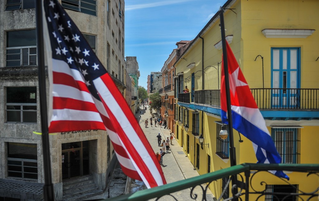 Cuban and US flags are seen outside the private restaurant La Moneda Cubana in Havana on March 17, 2016. Hundreds of workers have been scrambling for days to touch up building facades, patch potholes and spiff up Havana's monuments ahead of US President Barack Obama's visit. Obama next week will become the first US president to visit Cuba while in office in almost a century. AFP PHOTO/YAMIL LAGE / AFP / YAMIL LAGE