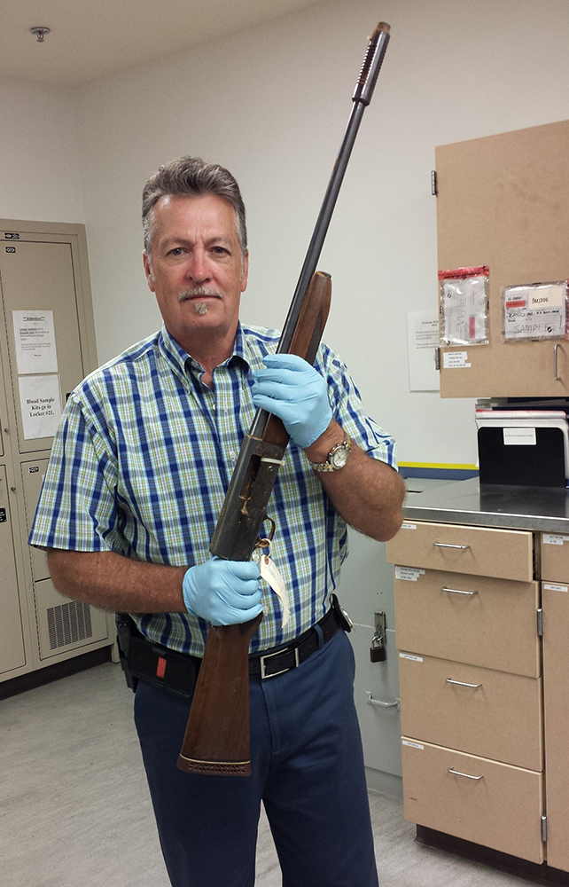 In this June 2015 photo released by the Seattle Police on Thursday, March 17, 2016, Detective Michael Ciesynski holds the shotgun which rock legend Kurt Cobain used to kill himself on April 8, 1994. Police did not say why they took the photos last year or why they're releasing them to the public at this time. (Seattle Police via AP)